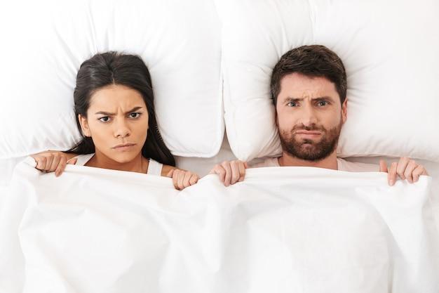 Uma briga descontente, um jovem casal apaixonado está deitado na cama, debaixo do cobertor