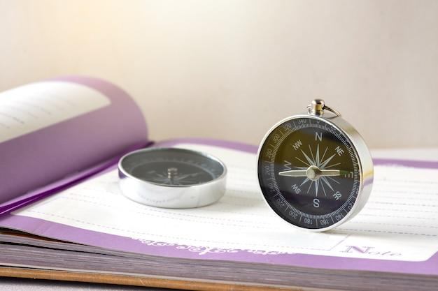 Uma bússola é colocada em um caderno em branco na mesa de trabalho. conceito de negócio e educação