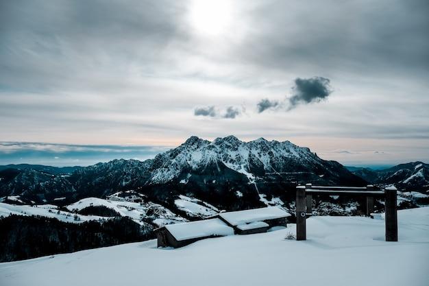Uma cabana coberta de neve com uma bela vista das montanhas cobertas de neve