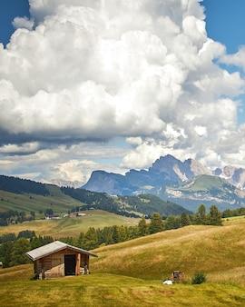 Uma cabana de madeira em uma terra verde sob nuvens brancas com belas montanhas