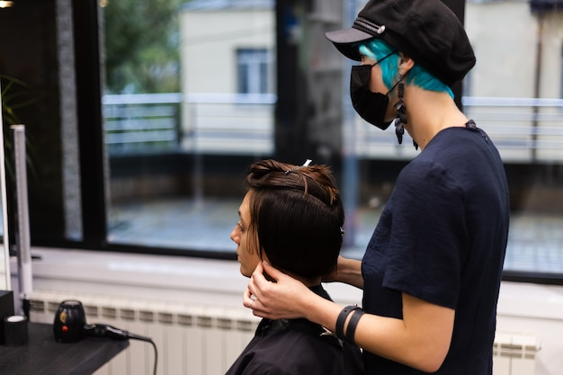Uma cabeleireira profissional faz o corte de cabelo de um cliente. a menina está sentada com uma máscara no salão de beleza