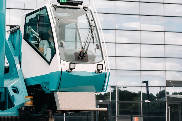 Uma cabine com o operador de um grande guindaste azul que está pronto para operar em suportes hidráulicos em uma plataforma próxima a um grande edifício moderno.