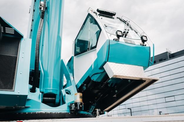 Uma cabine com o operador de um guindaste de carro grande azul que está pronto para operar em suportes hidráulicos em uma plataforma