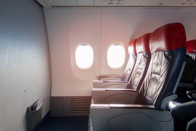 Uma cabine de aeronave com fileiras vazias de assentos para passageiros.