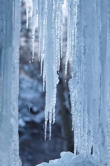 Uma cachoeira congelada com gelo nas cores azul e branca no inverno