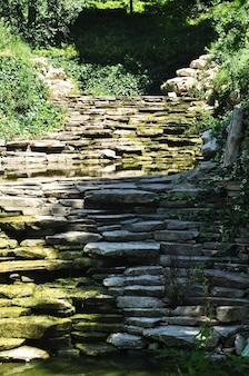 Uma cachoeira em cascata feita de pedras planas. cachoeira seca no verão quente.