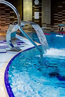 Uma cachoeira turquesa, massagem nas costas e nos ombros na piscina.