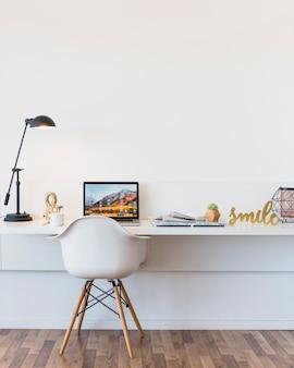 Uma cadeira branca vazia na frente da mesa com laptop e peça de show