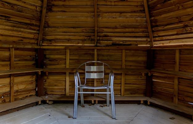 Uma cadeira de aço inoxidável na casa de madeira