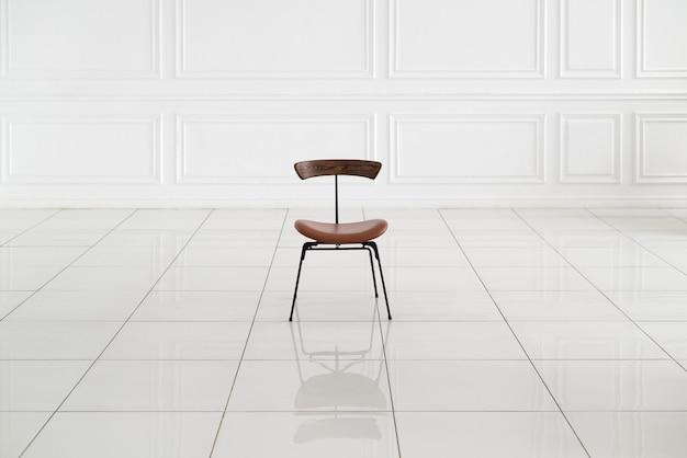 Uma cadeira de couro fica no meio de uma sala vazia com paredes e piso brancos
