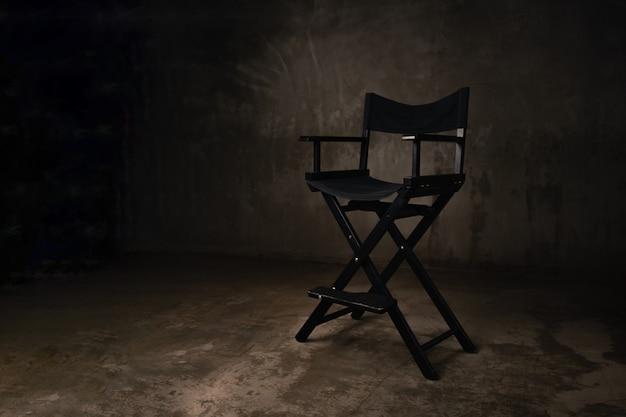 Uma cadeira de madeira preta fica em um estúdio de fotografia no contexto de um muro de concreto velho e arranhado.