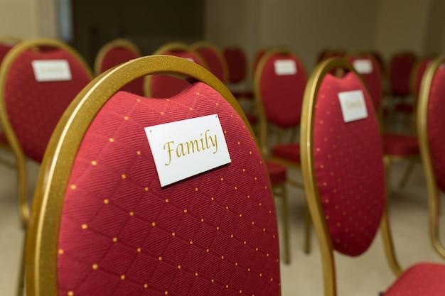 Uma cadeira em veludo vermelho com ouro e uma família de placa de identificação