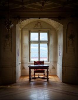 Uma cadeira solitária e mesa em uma ampla sala do castelo savoia, construída no típico estilo arquitetônico de walsen.