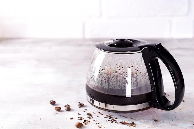 Uma cafeteira cheia com grãos de café contra um fundo cinza de pedra