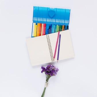 Uma caixa aberta de lápis de cor com notebook de linha única e flores de lavanda em fundo branco