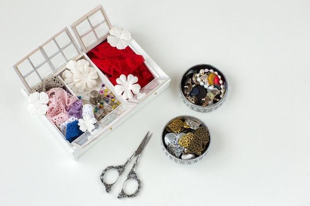 Uma caixa artesanal, há fitas de renda, agulhas, flores, tesouras, pingentes, botões, pérolas