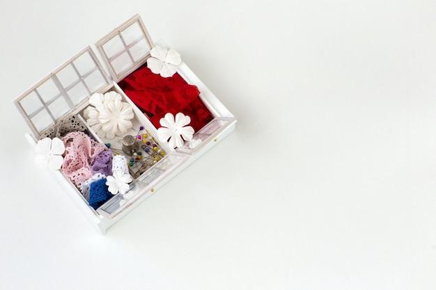 Uma caixa artesanal, há fitas de renda, agulhas, flores