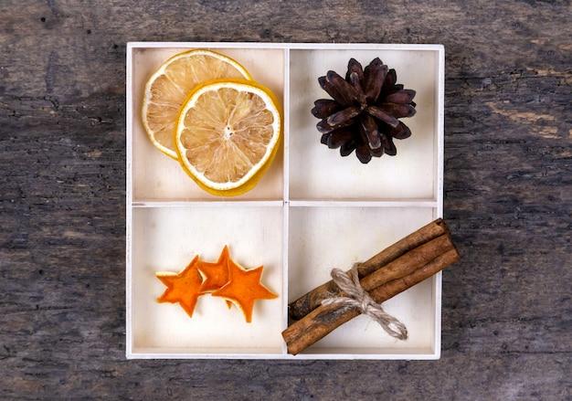 Uma caixa branca com compartimentos em um fundo de madeira cheia de paus de canela, laranjas secas, estrelas de tangerina e cone de árvore