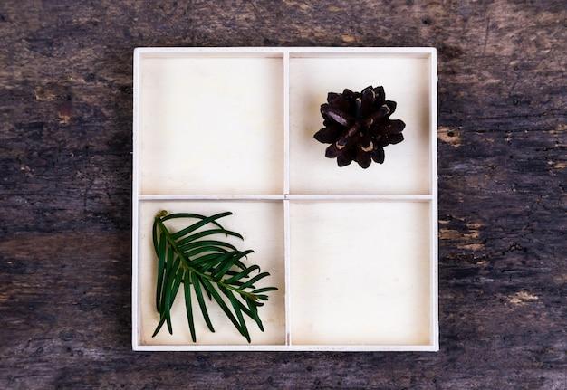 Uma caixa branca com compartimentos em um fundo de madeira cheia de pinhas e pinheiros