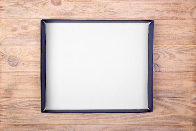Uma caixa branca vazia em branco sobre a mesa da mesa. vista do topo
