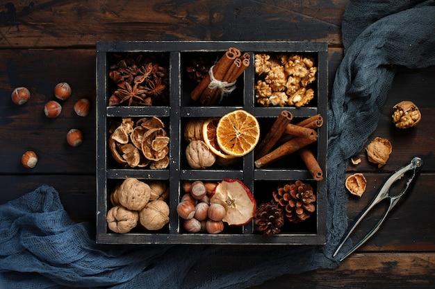 Uma caixa cheia de especiarias e nozes em uma vista de mesa de madeira