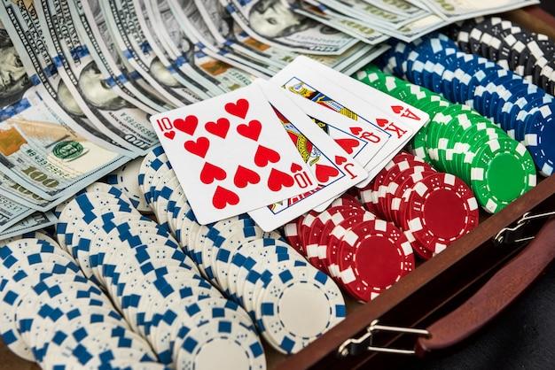 Uma caixa cheia de fichas, dólares e cartas de jogar no preto