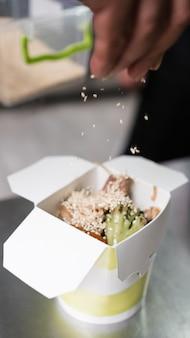 Uma caixa com comida asiática para viagem em cima da superfície de metal. entrega rápida e conveniente em restaurante