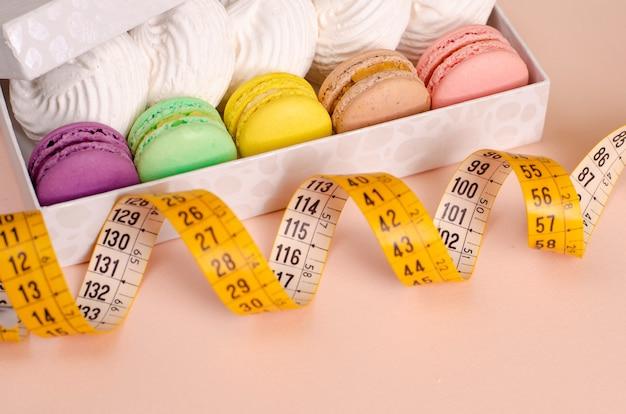 Uma caixa com macaroons e merengues e fita de medição na cor-de-rosa.