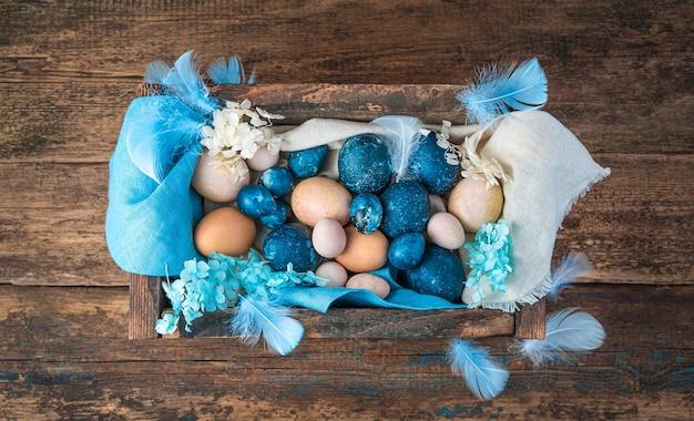 Uma caixa com ovos de páscoa em cores azuis e naturais sobre um fundo de madeira.