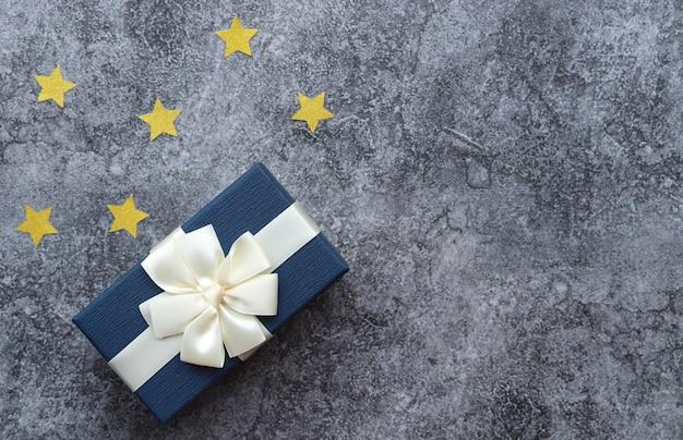 Uma caixa com um presente para um homem, uma superfície de concreto cinza