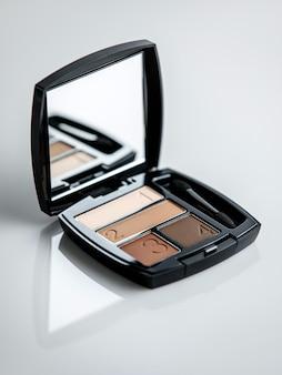 Uma caixa de blush vista frontal com blush e espelho em caixa preta na parede branca