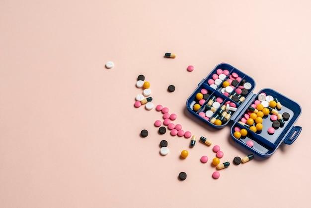 Uma caixa de comprimidos de plástico com um monte de farmácias de medicamentos de pílulas coloridas para tratamento