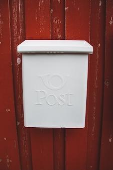 Uma caixa de correio branca em uma parede de madeira vermelha com uma porta vermelha.