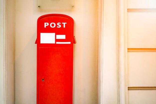 Uma caixa de correio vermelha perto da parede na cidade