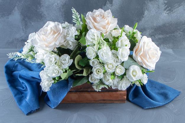 Uma caixa de flores brancas com toalha, na mesa branca.