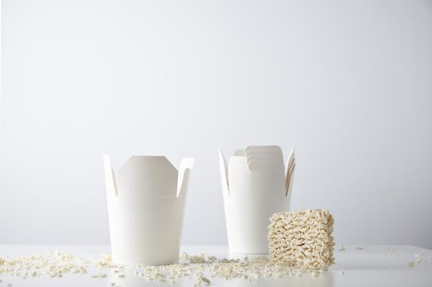 Uma caixa de macarrão para viagem aberta na frente de muitas outras dobradas apresentadas perto do pacote de macarrão comprimido seco com migalhas na mesa branca isolada