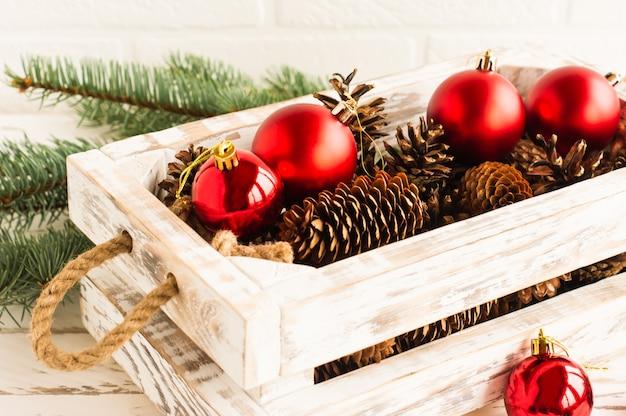 Uma caixa de madeira artesanal branca com bolas vermelhas de natal e ramos de abeto com cones em uma mesa de madeira. vista de perto.