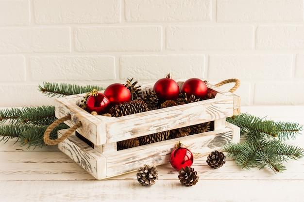 Uma caixa de madeira artesanal branca com bolas vermelhas de natal e ramos de abeto com cones em uma mesa de madeira.