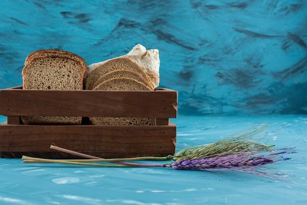 Uma caixa de madeira cheia de fatias de pão fresco marrom com espigas de trigo sobre fundo azul.