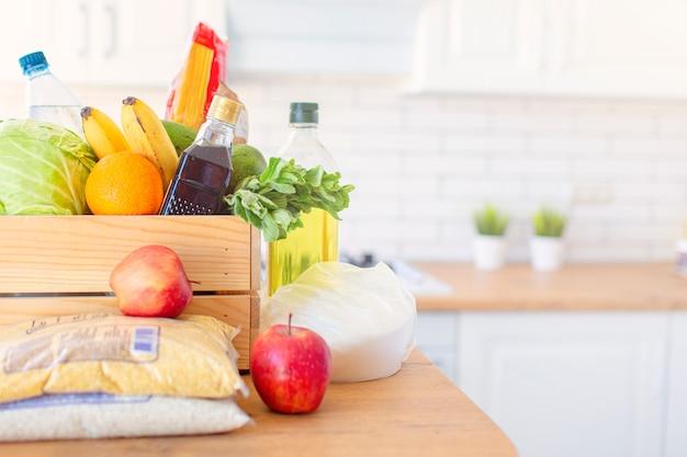 Uma caixa de madeira de diferentes alimentos, frutas, legumes, óleo, água, açúcar na cozinha. entrega em domicílio segura. copyspace.