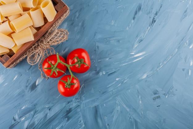 Uma caixa de madeira de massa crua seca com tomates vermelhos frescos em uma mesa de mármore.