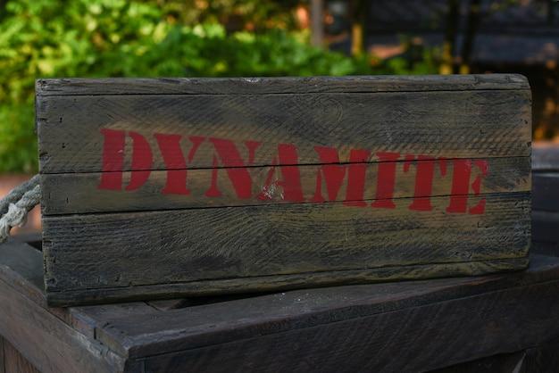 Uma caixa de madeira velha com uma dinamite vermelha da inscrição está na rua na perspectiva das folhas verdes.
