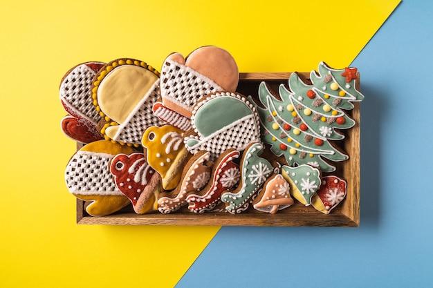 Uma caixa de natal gingerbread em fundo amarelo e azul. floco de neve, pinheiro, luva, abeto, estrela, trenó, cones, cone, estrela, forma de sino.