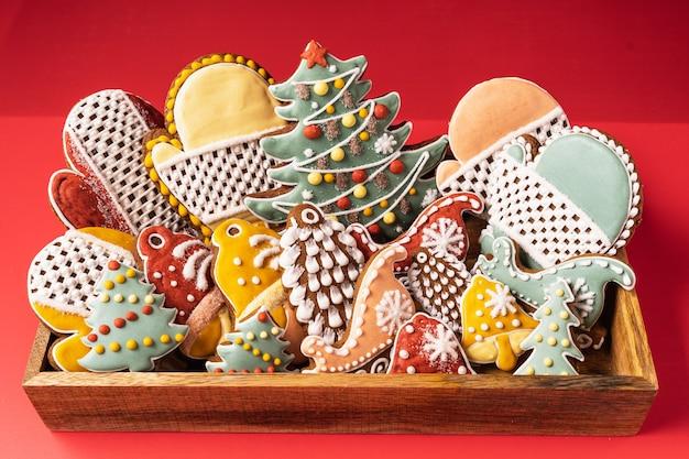 Uma caixa de natal gingerbread em fundo vermelho. floco de neve, pinheiro, luva, abeto, estrela, trenó, cones, cone, estrela, forma de sino.