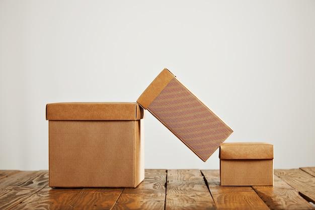 Uma caixa de papelão alta equilibrada em cima de duas caixas semelhantes com tampas em um ambiente de estúdio isolado no branco