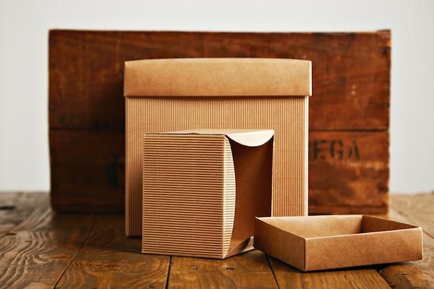 Uma caixa de papelão bege aberta e outra fechada ao lado de uma caixa de madeira marrom rústica isolada no branco