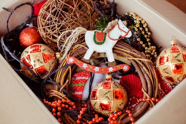 Uma caixa de papelão com brinquedos de natal para decorar a árvore de natal.