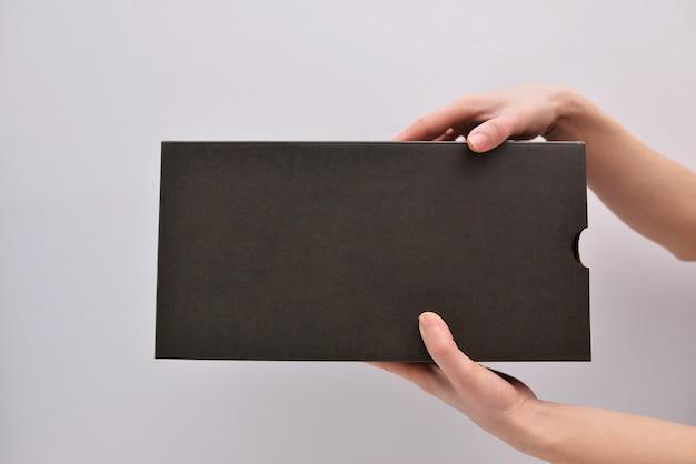 Uma caixa de papelão com espaço para texto nas mãos das mulheres. trabalho do serviço de entrega, entrega em domicílio. brincar. espaço para texto.