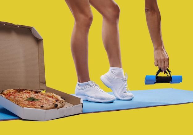 Uma caixa de pizza saborosa fresca, pernas de mulher ajustadas irreconhecíveis em um tapete de ioga e mão segurando halteres isolados. conceito de perder peso e engordar. conceito de fitness e dieta.