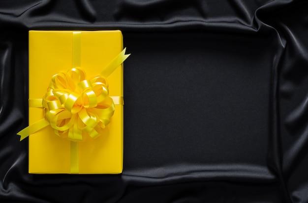 Uma caixa de presente amarela com fita é colocada em um pano preto liso e ondulado com espaço para texto. sexta-feira negra e conceito de boxing day.